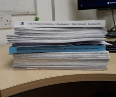 Pile of paperwork including IET Wiring Regulations and Code of Practice for the Safe Use of Lifting Equipment